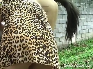 Big-breasted babe sucking on a horse's huge cock